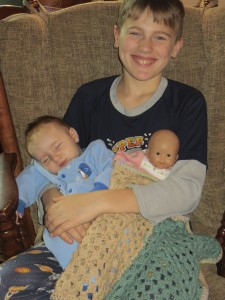 Matthew (13) holds Valor (3 months) for mom and a baby doll for Bella (2)
