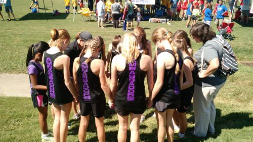 The girl's middle school team praying before their first race.